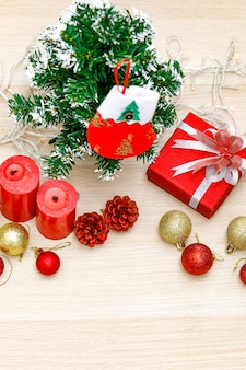 Set of christmas decorative items red and gold shiny glossy sphere balls candles present gift box with silver ribbon bowtie light bulb rope pine seeds xmas mockup tree with hanging sock on wood table.