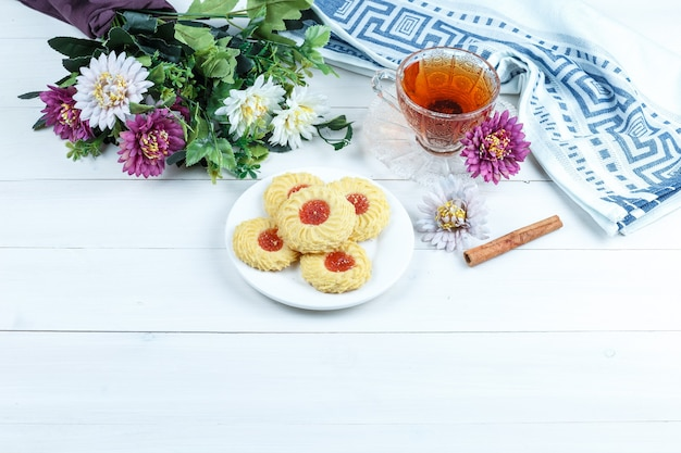 Set of cinnamon, cup of tea, kitchen towel and cookies, flowers on a white wooden board background. high angle view.