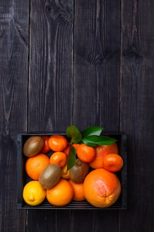 A set of citrus fruits to enhance immunity in a black box on a dark background. the concept of raising immunity. copy space