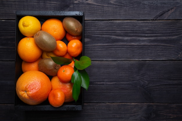 A set of citrus fruits to enhance immunity in a black box on a dark background. the concept of raising immunity.