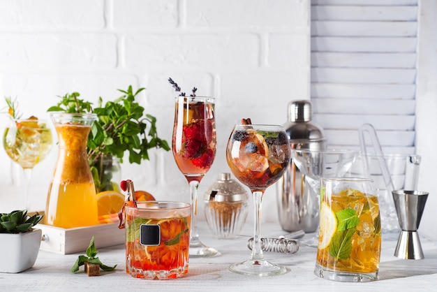 Set of classic cocktails with bar accessories on white wooden backgorund
