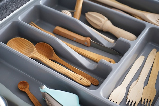 Set of clean kitchen utensils in drawer.