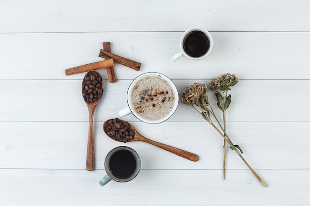 Set of coffee beans, cinnamon sticks, dried herbs and coffee in cups on a wooden background. top view.