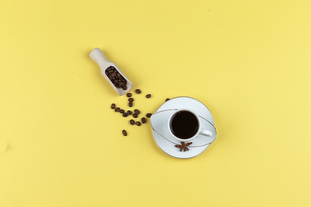 Set of coffee beans and coffee in a cup on a yellow background