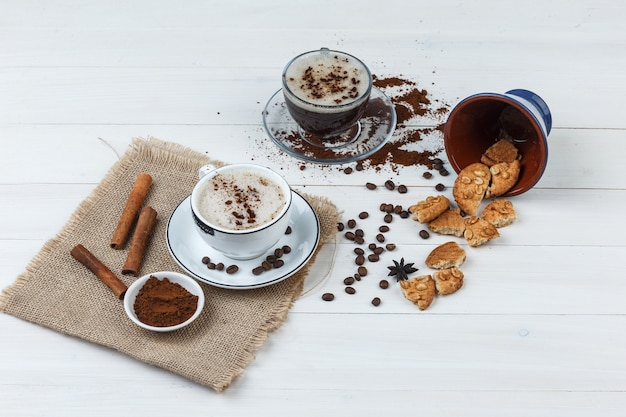 Set of coffee beans, grinded coffee, cookies, cinnamon sticks and coffee in cups on wooden and piece of sack background. high angle view.