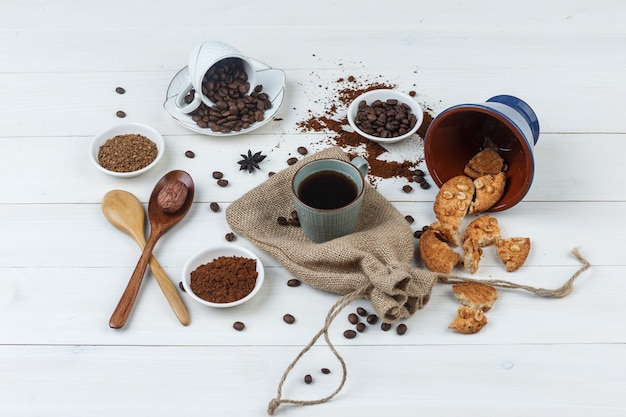 Set of coffee beans, grinded coffee, cookies, wooden spoons and coffee in a cup on wooden and sack background. high angle view.