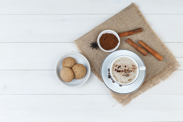 Set of coffee beans, grinded coffee, spices, cookies and coffee in a cup on wooden and piece of sack background. top view.