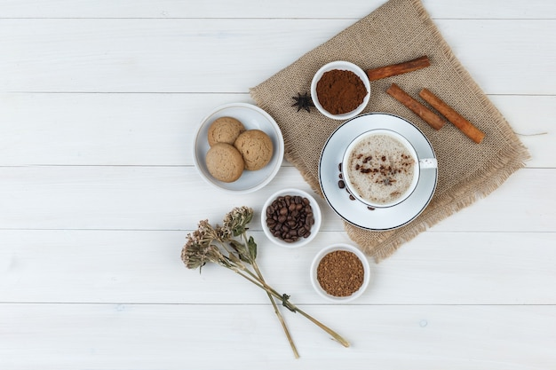 Set of coffee beans, grinded coffee, spices, cookies, dried herbs and coffee in a cup on wooden and piece of sack background. top view.