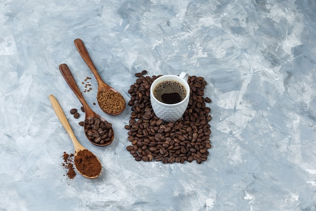 Set of coffee beans, instant coffee, coffee flour in wooden spoons and cup of coffee on a light blue marble background. close-up.