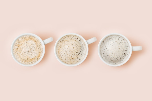 Set of coffee cups assortment on pale pink background. flat lay, top view collection