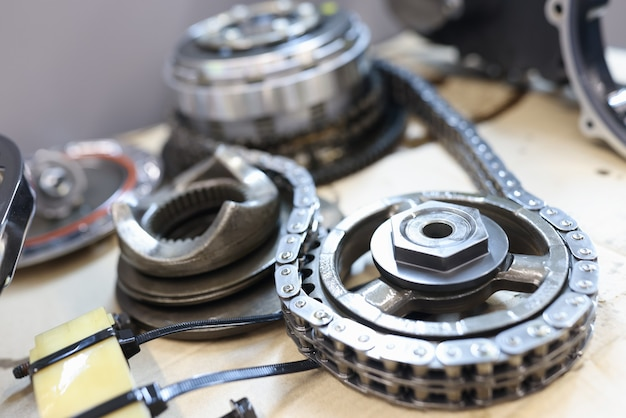 Set of cogwheels connected with steel chain lying at service table waiting to be checked and