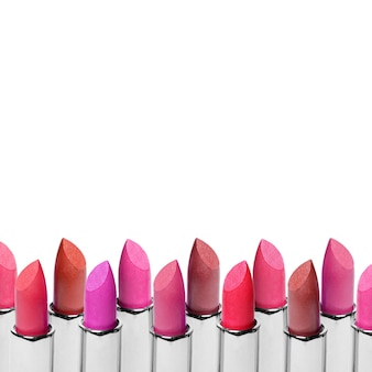 Set of color lipsticks arranged in line isolated on white surface