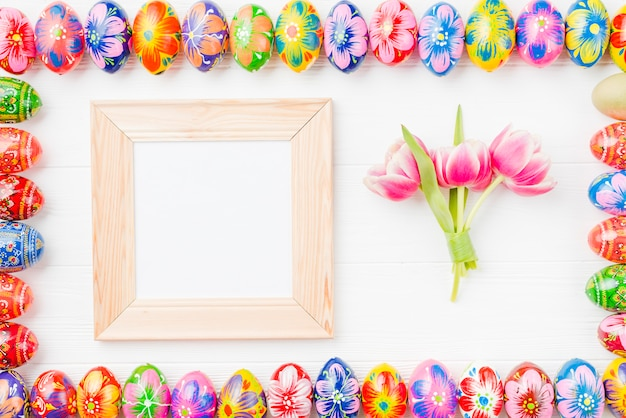 Set of colored eggs on edges, frame and flowers