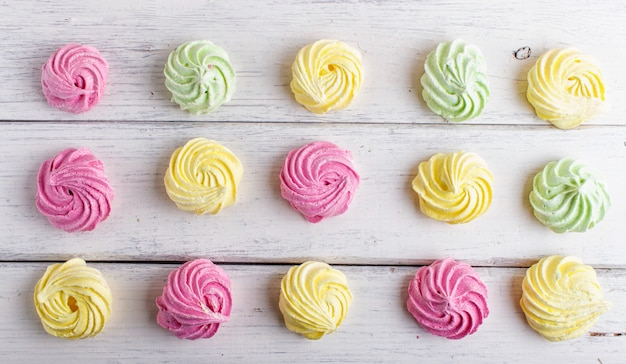 Set of colored meringues on white wooden background. geometric pattern.