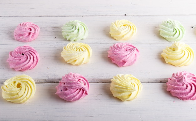 Set of colored meringues on white wooden background geometric pattern