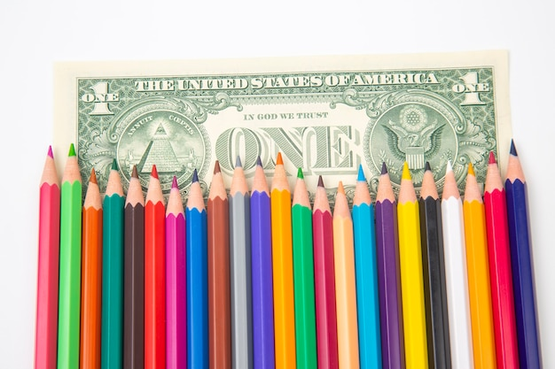 Set of colored pencils for drawing on a dollar background. sales marketing