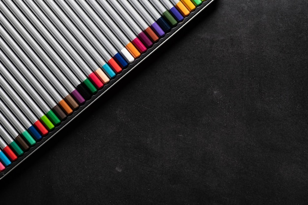 A set of colored pencils for pastels on a black magnetic board for notes on the refrigerator