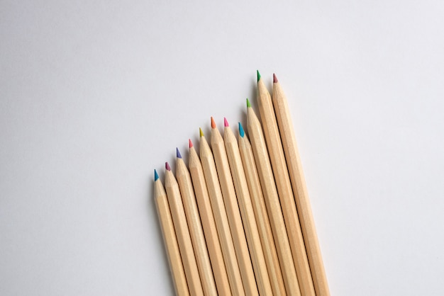 Set of colored pencils on white paper