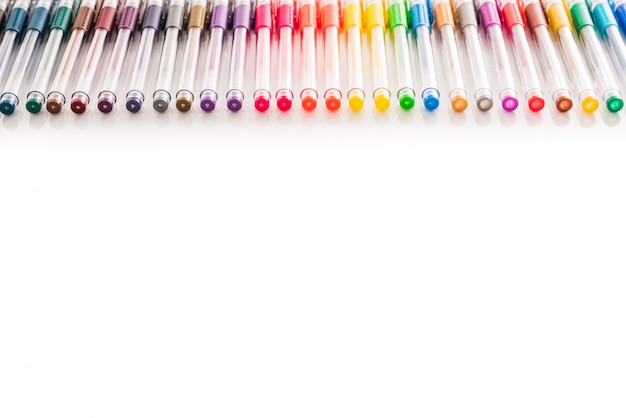 Set of colored pens arranged on a white studio table with isolated copy space.