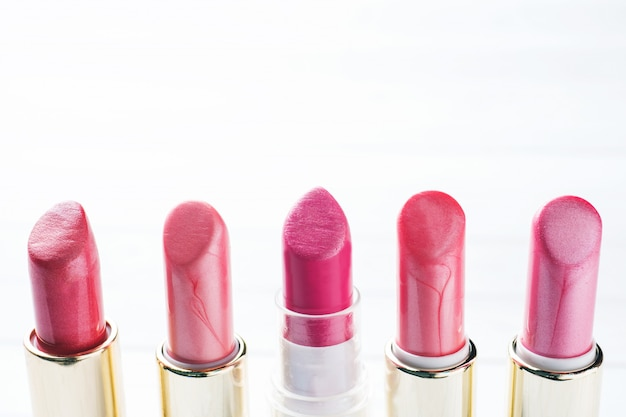 Set of colored pink lipsticks on white background. women's cosmetics. selective focus. copy space.