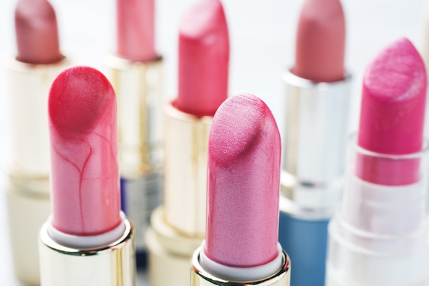 Set of colored pink lipsticks on white background. women's cosmetics. selective focus.