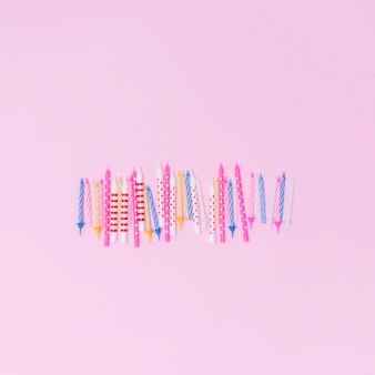 Set of colorful candles on pink background