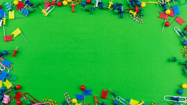 Set of colorful color push pins thumbtacks frame top view isolated on green background