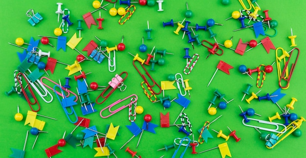 Set of colorful color push pins thumbtacks top view isolated on green background