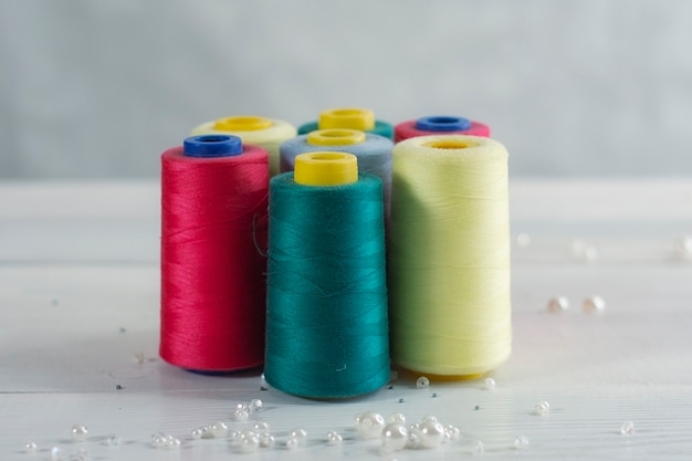 Set of colorful colored balls of thread on a light-colored wooden background.