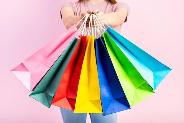Set of colorful holiday bags in woman hands