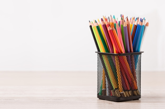 Set of colorful pencils standing at black metallic container on a wooden table. copyspace