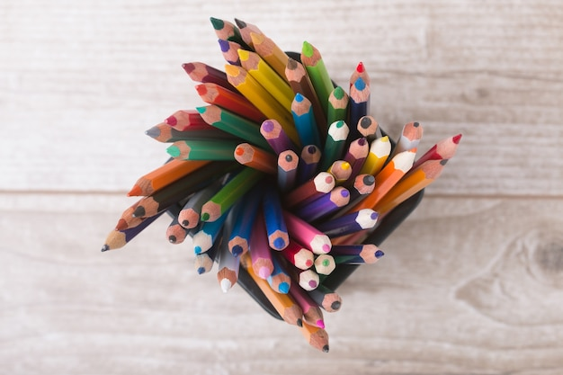 Set of colorful pencils standing at black metallic container on a wooden table. top view