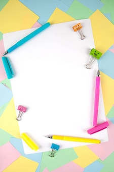 Set of colorful pens, sticky notes, notepads, pens, binderclips. top view