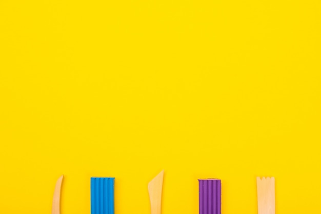 Set of colorful plasticine isolated on yellow background