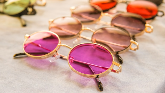 Set of colorful sunglasses for sale in a store. different sunglasses on light coloured background. summer eyeglasses.fashion collection