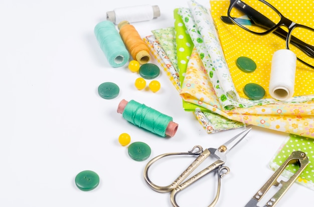 Set of colorful yellow and green fabrics, scissors, buttons, spools of thread and glasses