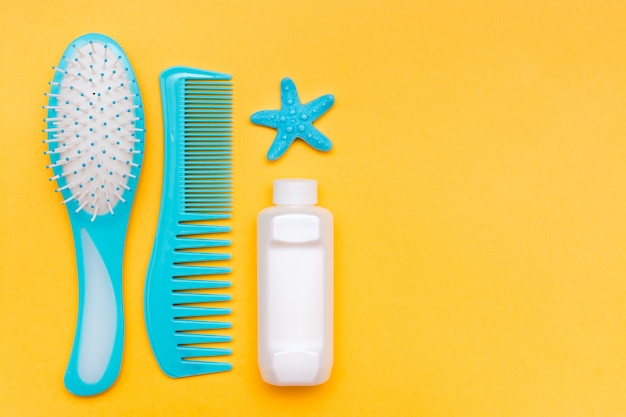 A set of combs, a bottle of balsam and a hair clip on a yellow  top view