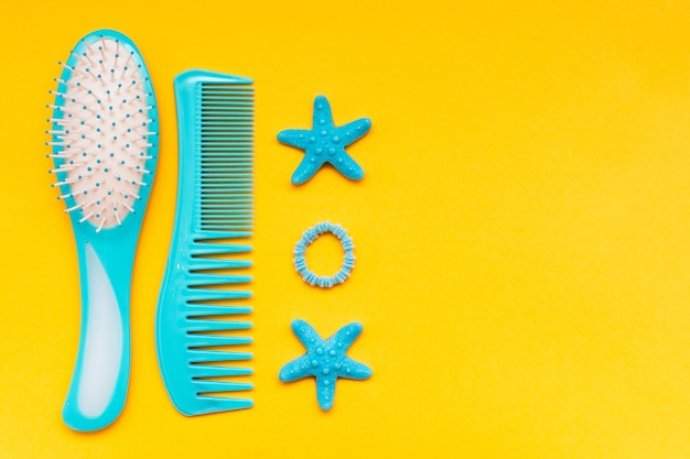 A set of combs, a hair band and a hair clip on a yellow  top view