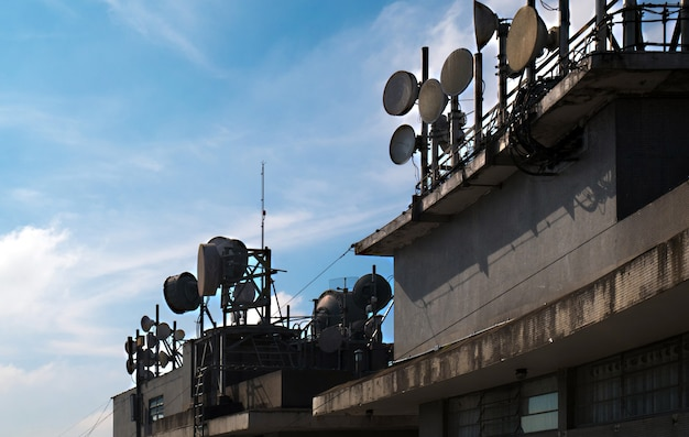 Set of communication antennas on a building rooftop.
