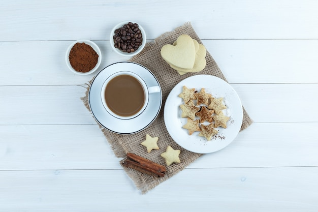Set of cookies, cinnamon sticks, coffee beans, grinded coffee and coffee in a cup on wooden and piece of sack background. top view.