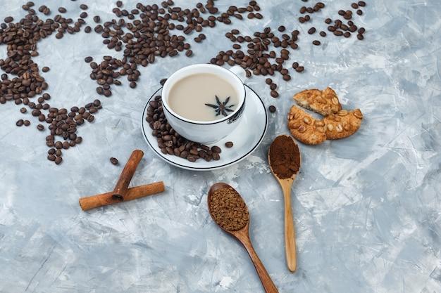 Set di biscotti, chicchi di caffè, caffè macinato, bastoncini di cannella e caffè in una tazza su uno sfondo di gesso grigio. vista ad alto angolo.