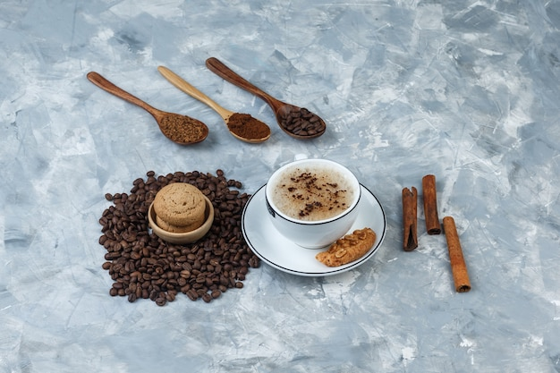 Set of cookies, coffee beans, grinded coffee, cinnamon sticks and coffee in a cup on a grungy grey background. high angle view.