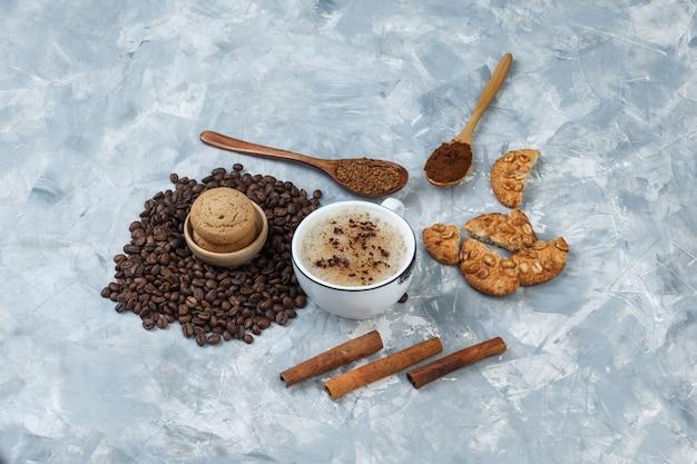 Set di biscotti, chicchi di caffè, caffè macinato, bastoncini di cannella e caffè in una tazza su uno sfondo grigio sgangherato. vista ad alto angolo.