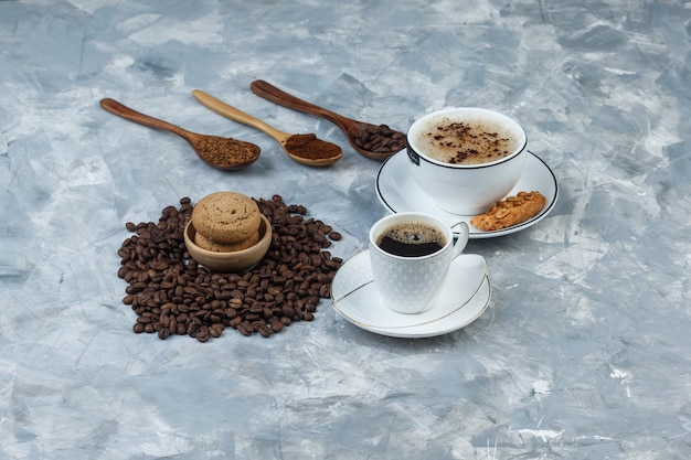 Set of cookies, coffee beans, grinded coffee and coffee in cups on a grungy grey background. high angle view.