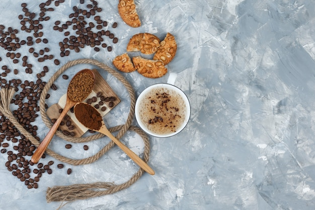 Set of cookies, coffee beans, grinded coffee, rope and coffee in a cup on grey plaster and wood piece background. top view.