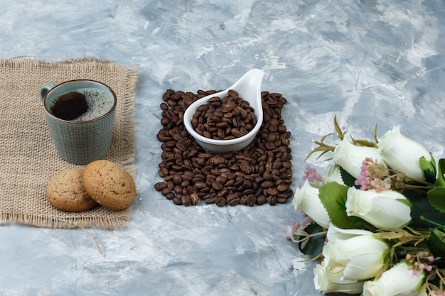 Set of cookies, cup of coffee, flowers and coffee beans in a white porcelain jug on a blue marble background. close-up.