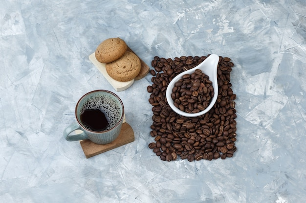 Set of cookies on a cutting board, cup of coffee and coffee beans in a white porcelain jug