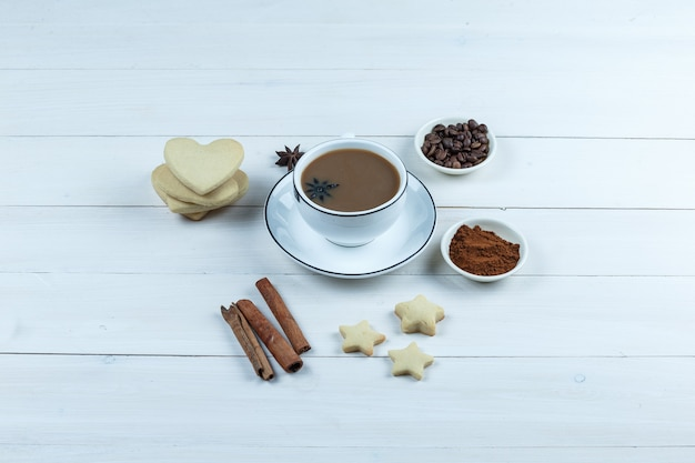 Set of cookies, spices, coffee beans, grinded coffee and coffee in a cup on a wooden background. high angle view.