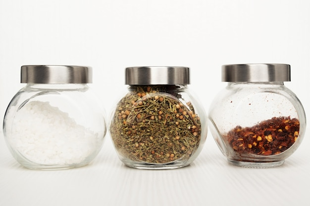 Set for cooking delicious dishes. sea salt, mix of herbs, hot chili pepper on a white background