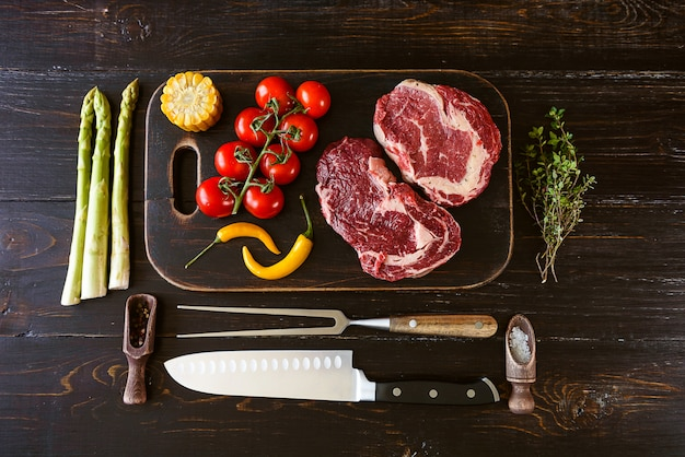 Set for cooking a festive dinner for two. two raw marbled beef steaks, spices, vegetables